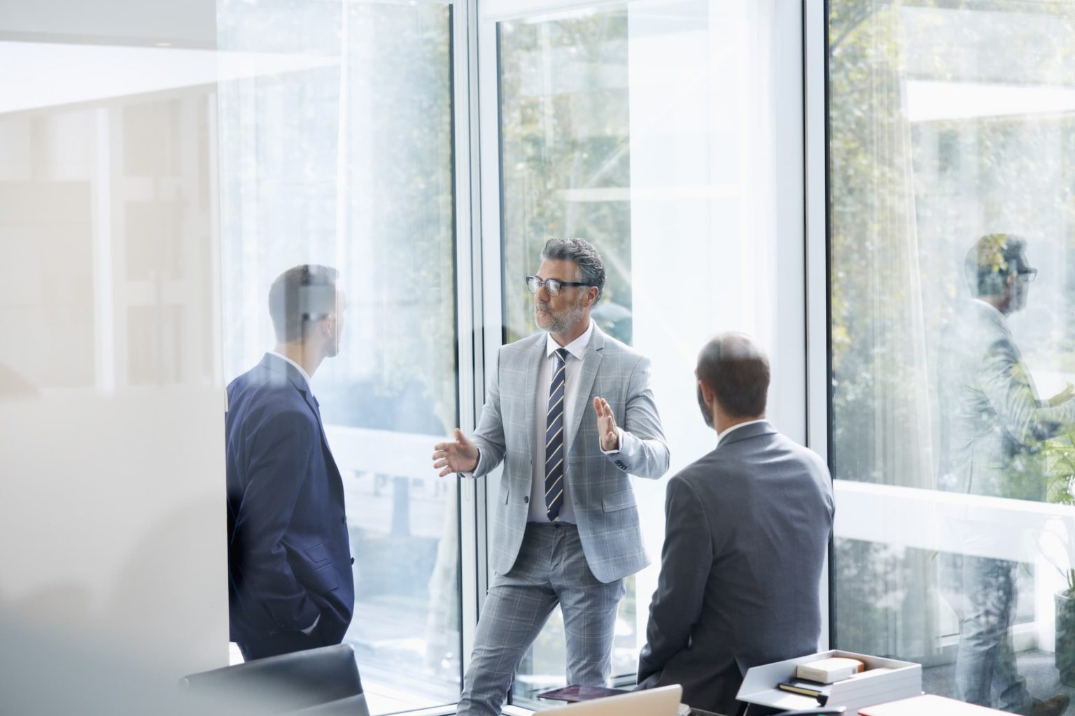 Confident businessman discussing with colleagues in meeting by window at office