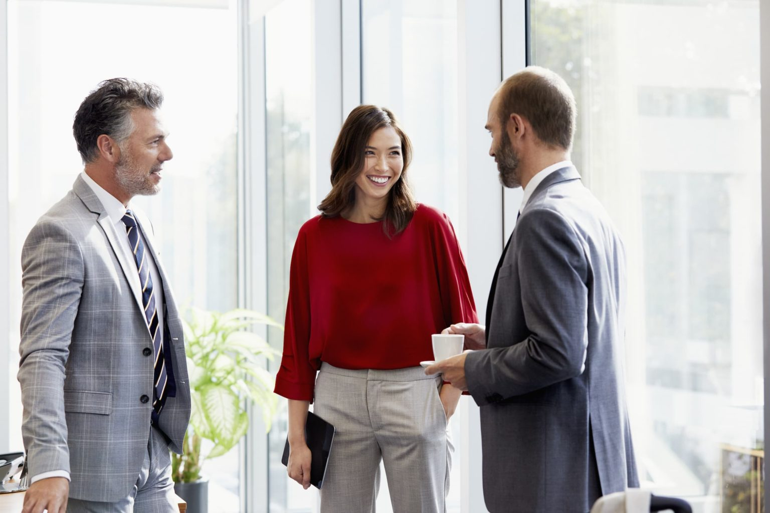 Smiling business people discussing in meeting while standing by glass window at office